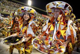 23日、ブラジル・リオデジャネイロのカーニバルで、トップチームのパレードで踊る参加者(共同)