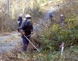福島県葛尾村の「特定復興再生拠点区域」で草を刈る除染作業員=20日午前