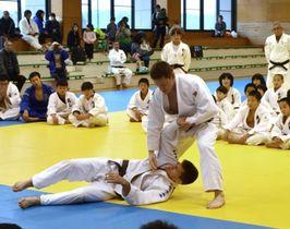 小中高生に技を見せるスロベニアの選手とコーチ(いずれも中央)=鹿屋市向江町の市武道館