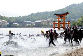 厳島神社の大鳥居を背に、水しぶきを上げて一斉にスタートする選手(16日午前8時)