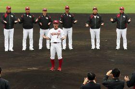 日本ハムとの練習試合後、岡島選手会長(中央)が音頭を取り、一本締めで初の金武キャンプを打ち上げた=23日、金武町ベースボールスタジアム