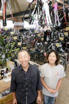 熊本市の店舗が取り壊しになり、山鹿市に移転した大薮建二さんと長女さおりさん。新店舗の机やラックは常連客の手作り=7日、山鹿市