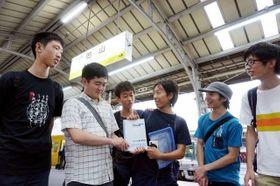 """被災地へのメッセージを記したノートを手にする学生ら。今月6日にはJR岡山駅で""""バトン""""をつないだ"""