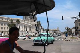 キューバの首都ハバナの街中を走るクラシックカー。手前は人力タクシーだ(C)Kasumi Abe
