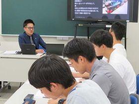 吉岡専務(左端)から商品開発の流れを聞く県立大の学生