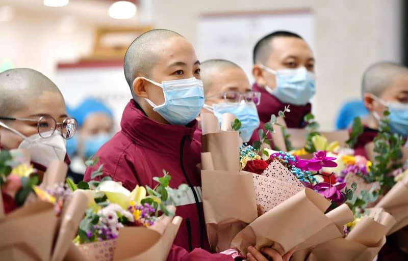 中国甘粛省で頭を丸刈りにして壮行会に臨む医療チームの女性ら=15日(新華社=共同)