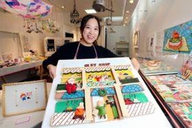企業広告用にお菓子で作った絵を手にするイトウユカさん=芦屋市茶屋之町