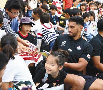 ロシア戦から一夜明け、子どもたちと交流するラグビー日本代表のラファエレ選手(右)ら=21日午後、秩父宮ラグビー場で