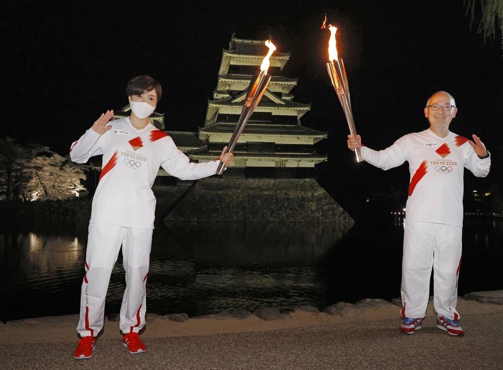 前走者(右)から聖火を引き継ぎ、松本城前でポーズをとる小平奈緒さん=2日夜、長野県松本市