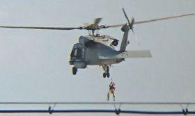 米海軍のHH60Hヘリから降下訓練をする兵士=18日、米軍嘉手納基地上空