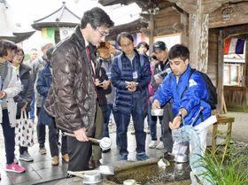 「ウオッシュ・ユア・ハンズ」。参拝時の作法を外国人に教える方法を学ぶ参加者(四万十町茂串町の岩本寺)