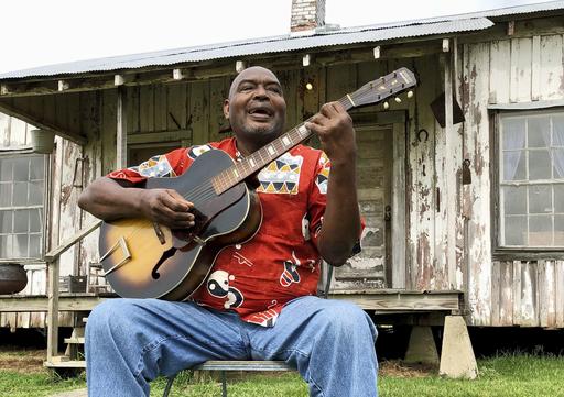 かつての大農園の小作人小屋の前で「シェアクロッパーズ・ブルース」を歌うシンガー兼ギタリストのベン・ペイトン=19年8月、米ミシシッピ州グリーンウッド(共同)