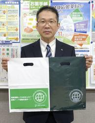 配布した節薬バッグを持つ福岡市薬剤師会の木原太郎副会長(同会提供)