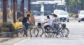 「逃げ水」現象でタイヤが溶けたように見える自転車=25日午後1時42分、岡山市中心部の桃太郎大通り