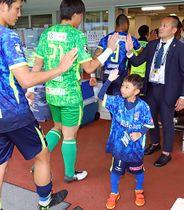 試合後、モンテディオ山形の選手をハイタッチで迎える富樫陽向君(手前右)