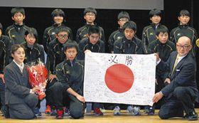 寄せ書きをした日の丸を掲げる川上中スケート部員と父の徳隆さん(前列右)。前列左は母の治枝さん=川上村で