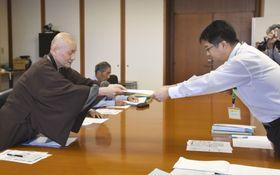 原発再稼働時の「地元同意」の対象を拡大した協定締結を求め、福井県小浜市に要請書を手渡す市民団体のメンバー(左)=24日午後、小浜市役所