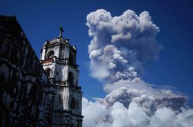 ルソン島南部マヨン山の麓にあるレガスピ・ダラガの街から見える噴煙=22日(AP=共同)