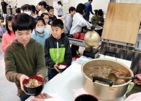 作った淡路島牛丼を取り分けてもらう子どもたち=美菜恋来屋