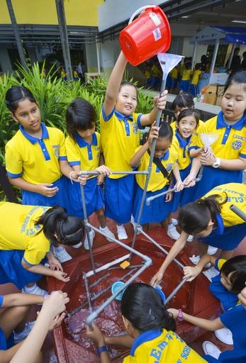 「給水制限訓練」でパイプをつなぎ、水が運ばれる仕組みを学ぶクレメンティ小の児童。政府は次世代の節水教育に力を入れている=3月、シンガポール(共同)