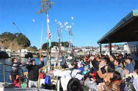 漁船から餅がまかれ、多くの町民や観光客らが詰め掛けた「乗り初め」=西伊豆町の仁科漁港