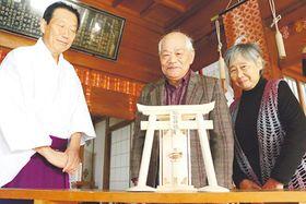 最後の仕事で手掛けた鳥居の模型を見つめる西川さん(中央)と鈴枝さん(右)