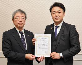 鞍田局長から委嘱状を受ける石田さん(右)