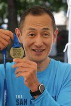 レース終了後、完走メダルを掲げて笑顔を浮かべる山中伸弥教授