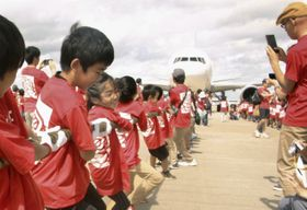 成田空港で開かれた「空の日」にちなんだイベントでジェット機を相手に綱引きする小学生=23日