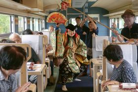 JR山陰線の倉吉―出雲市間で運行された「神話列車」で、石見神楽を鑑賞する乗客ら=12日