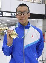 成田空港でメダルを手に笑顔の宮本陽輔=17日