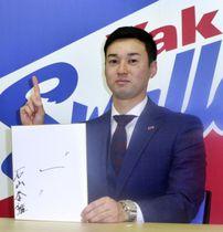 契約更改交渉を終え、記者会見で色紙を手にポーズをとるヤクルトの石山泰稚投手=12日、東京都内の球団事務所
