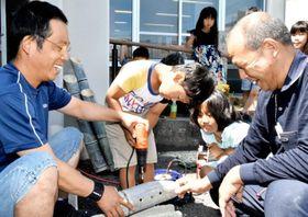 今治市乃万公民館の竹灯籠作りで、竹に穴を開ける参加者