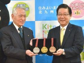 北九州エコタウン連絡会議の関和己会長(左)から金、銀、銅のリサイクルメダルを受け取る北九州市の北橋健治市長