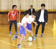 ボールを使って児童と触れ合う愛媛FCの前野貴徳選手(左)と川井健太監督(右)=23日午後、松前町西高柳