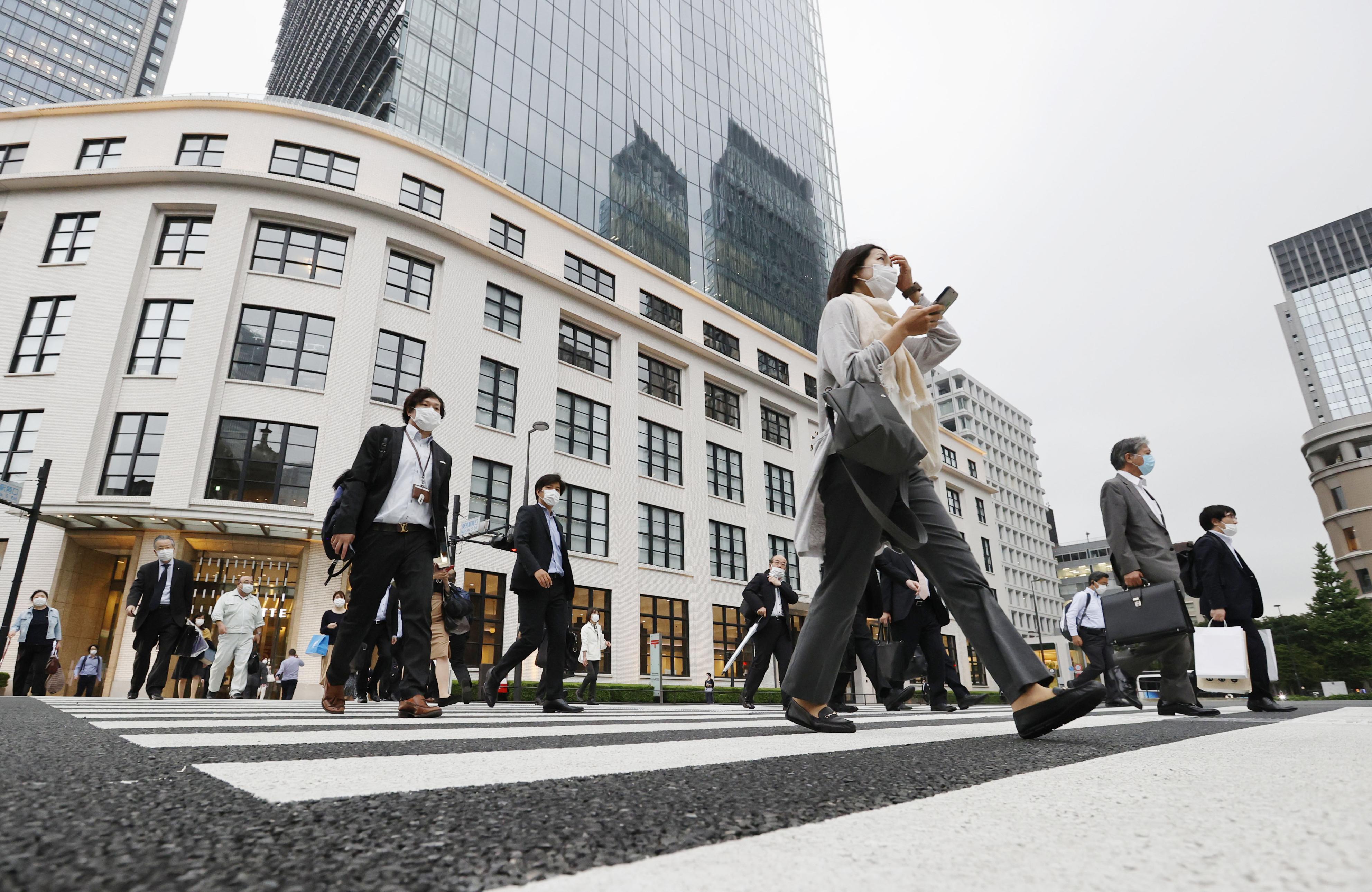 JR東京駅前を歩く人たち=18日午後