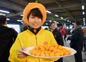 市場で完熟キンカン「たまたま」をPRする女性=15日午前、宮崎市