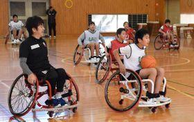 根木慎志さん(左)と車いすバスケットボールを楽しむ児童たち