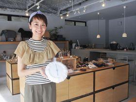 ニットを模した陶器の時計を手にするディレクターの仲川依利子さん=東京都墨田区