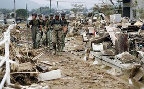 岡山県倉敷市の真備町地区で、行方不明者の捜索をする自衛隊員=12日午前9時30分