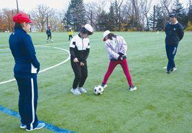 【写真=芳賀さん(右)から指導を受け、サッカーの練習を楽しむ虻田小の児童】