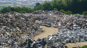 大量の災害ごみが積まれた仮置き場の吉備路クリーンセンター=昨年8月2日、倉敷市真備町箭田