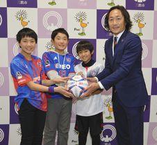 FC東京の石川直宏さん(右)から記念ボールを贈られ、喜ぶ児童ら=三鷹市役所で