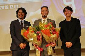 日本代表でチームメートだった中沢佑二さん(左)、楢崎正剛さん(右)から花束を受け取った闘莉王=東京都品川区