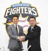 北海道日本ハムのスペシャルアドバイザーに就任する田中賢介氏(左)と握手を交わす球団の川村浩二社長(大島拓人撮影)
