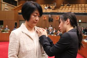 議員バッジを着けてもらう新議員=長崎市議会議場