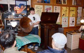 蓄音器にレコードをかける前田晋作さん(奥)=日置市日吉の「前田家」