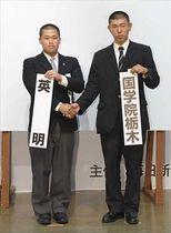対戦が決まり、英明の千原凌平主将(左)と握手する国学院栃木の大久保謙亮主将=16日午前、大阪市