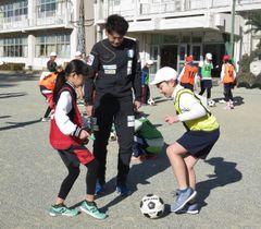 【選手に教わりながらサッカーを楽しむ児童ら=伊勢市東大淀町の東大淀小学校で】
