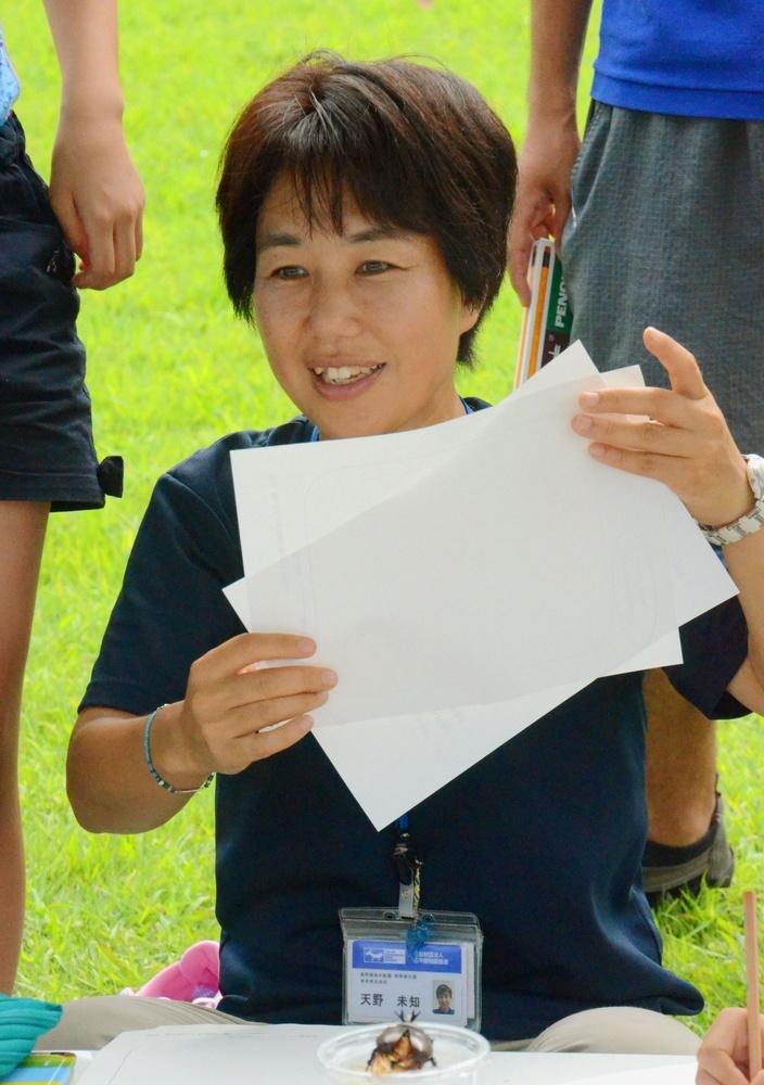 子どもたちの書いた生きものカードを手に話を聞く天野未知さん=東京・葛西臨海水族園